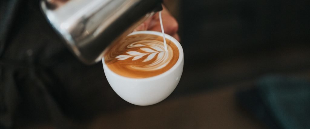 pouring steamed milk into a latte