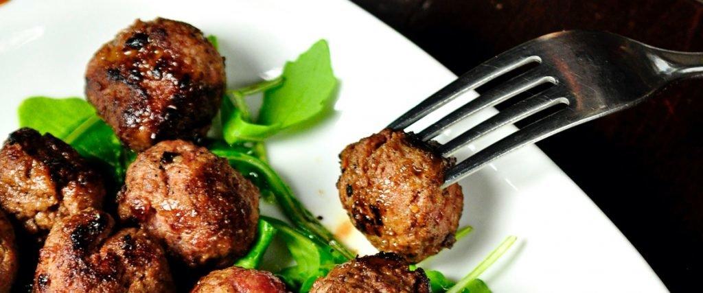 meatballs on bed of lettuce on white plate